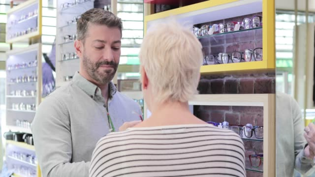 vidéos et rushes de customer trying frames at the opticians - opticien