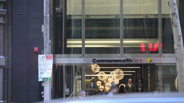 WS A customer uses a Commonwealth Bank of Australia automated teller machine WS signage for the Commonwealth Bank of Australia is displayed outside a...