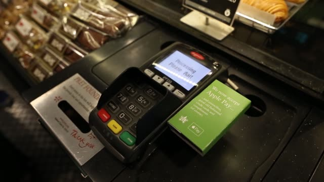 vídeos de stock, filmes e b-roll de a customer uses an apple inc iphone to pay via the apple pay system from their santander account at the checkout till inside a pret a manger ltd... - pagamento móvel
