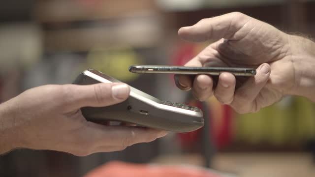 vídeos y material grabado en eventos de stock de customer uses an iphone to make a contactless payment for a purchase at a retail store, close up - mostrador de tienda para pagar