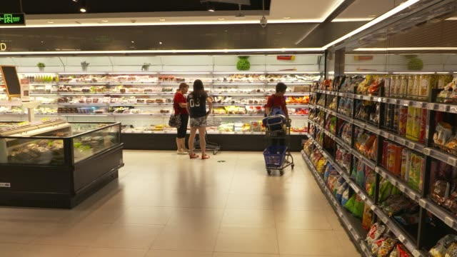 vidéos et rushes de a customer walks past signage for hema is displayed in an alibaba group holding ltd hema store in shanghai china on tuesday sept 12 customers look at... - store