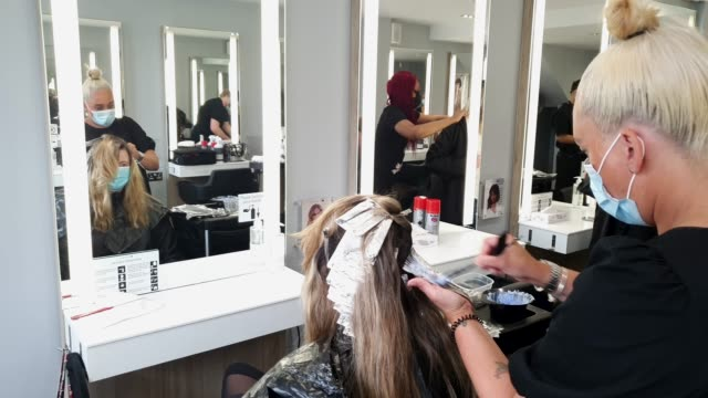 customer wearing a face mask gets her hair done by a hairdresser wearing a face mask at headmasters on july 4, 2020 in east dulwich, london, england.... - hairstyle stock videos & royalty-free footage