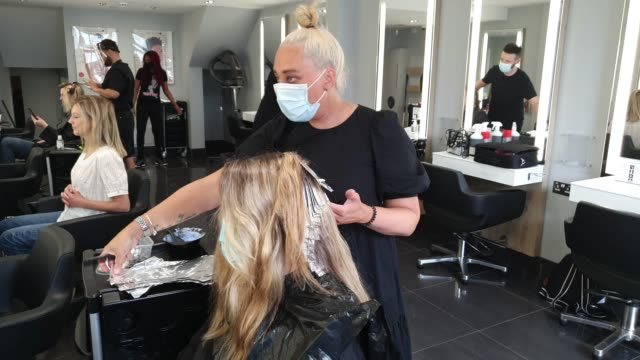 customer wearing a face mask gets her hair done by a hairdresser wearing a face mask at headmasters on july 4, 2020 in east dulwich, london, england.... - cutting hair stock videos & royalty-free footage