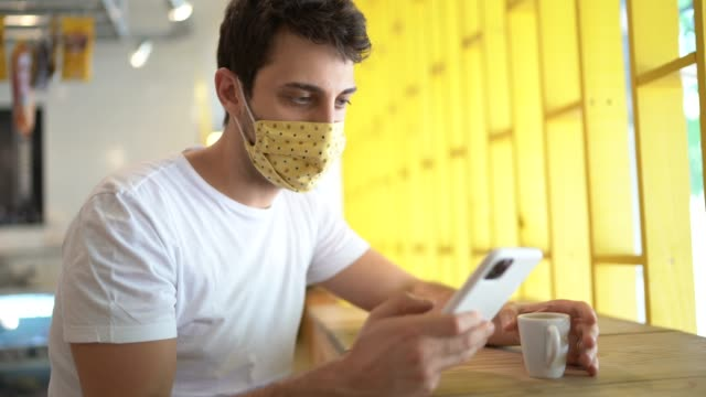 customer wearing face mask using smartphone and drinking a coffee in a coffee shop - brazilian ethnicity stock videos & royalty-free footage