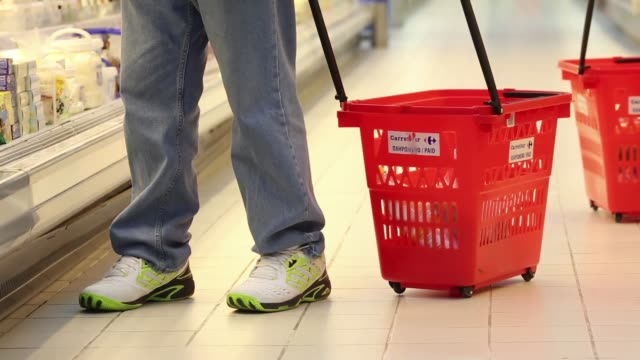a customer wheels a shopping basket along an aisle inside a carrefour sa supermarket part of the marinopoulos group at the mall of cyprus in nicosia... - キプロス ニコシア点の映像素材/bロール