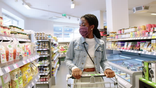 customer with mask walking in grocery store with a shopping cart - groceries stock videos & royalty-free footage