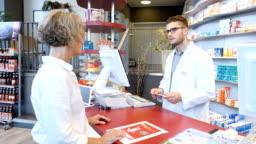 Customer with prescription talking to chemist