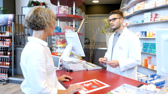 vídeos de stock e filmes b-roll de customer with prescription talking to chemist - cliente