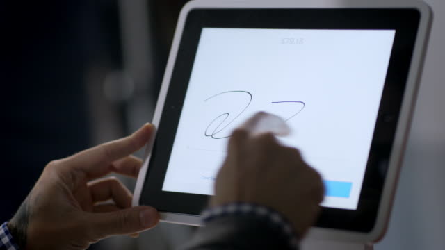 customer writes signature with index finger on tablet touchscreen at checkout counter in local shop - 署名点の映像素材/bロール