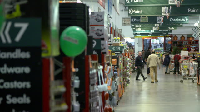 Customers and employees in aisles with products on display at Bunnings Warehouse hardware store