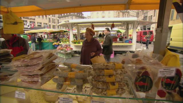 ms pan customers at meat and cheese stand at rathaus market, basel, switzerland - rathaus bildbanksvideor och videomaterial från bakom kulisserna