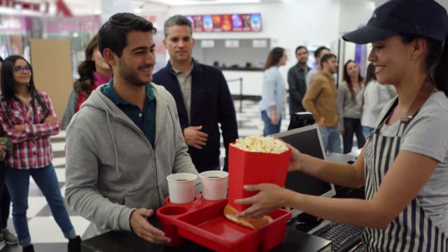 vídeos de stock, filmes e b-roll de clientes no stand de concessão de cinema comprando lanches para o filme - pipoca