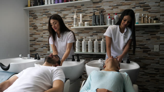 customers at the hair salon getting their a shampoo looking relaxed - beauty salon stock videos & royalty-free footage
