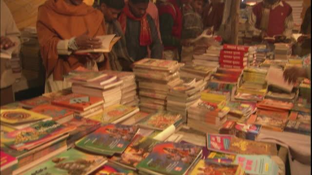 Customers browse books on market stall, Allahabad, Uttar Pradesh, India