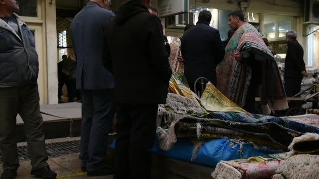 Customers browse carpets in the rug bazaar in Tehran Iran on Monday Jan 15 2018