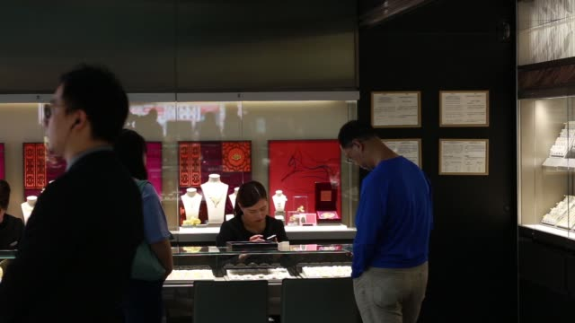 vidéos et rushes de customers browse jewelry inside the chow sang sang holdings international ltd jewelry store in the mong kok district of hong kong china on friday... - mong kok