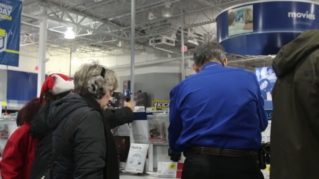 Customers browse the selection of electronics and equipment available for sale at Best Buy in Northbrook Illinois A young man looks at a speaker...