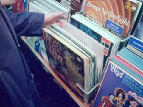 stockvideo's en b-roll-footage met customers browse the selection of lps in a record shop. - vinylplaat
