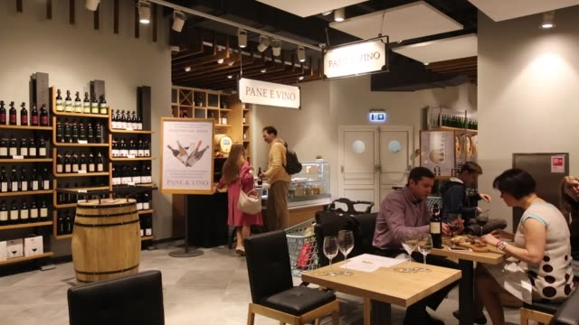 vídeos de stock, filmes e b-roll de customers browse wine and dine at the 'pave e vino' eatery inside the new eataly food store operated by eataly net srl at the kievsky shopping mall... - vino