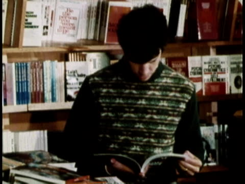 vídeos de stock, filmes e b-roll de 1979 montage customers browsing and buying books in bookstore / united states - livraria