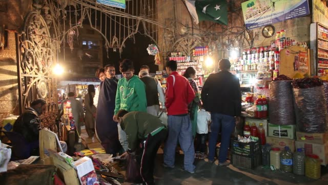 customers buy fruit and vegetables at an outdoor market at night in karachi, pakistan, on thursday, dec. 14 fruit vendors wait for customers at an... - ナイトイン点の映像素材/bロール