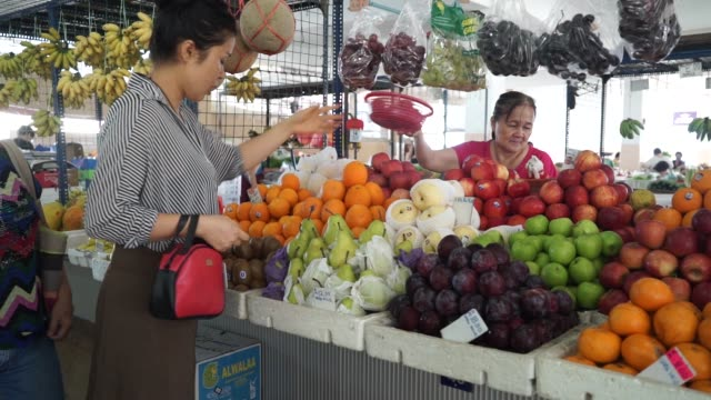 customers buy fruit at a fruit stall in stutong wet market in kuching, sarawak, malaysia, on wednesday, april 14 a customer selects kiwi fruit at a... - malaysia stock-videos und b-roll-filmmaterial