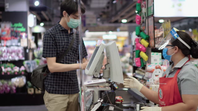 customers buying food and staples from a cashier and paying at the till. supermarket - shop assistant stock videos & royalty-free footage