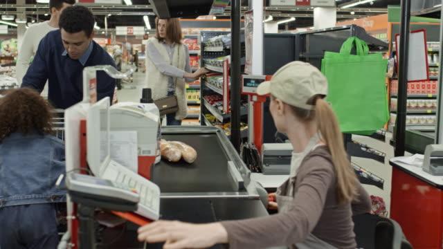 Customers buying groceries in supermarket