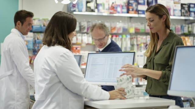 customers buying medicines from chemist at store - pharmacy stock videos & royalty-free footage