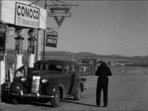stockvideo's en b-roll-footage met b/w 1934 pan customers + cars at conoco gas station in desert / sierra blanca, texas - kleine groep dingen