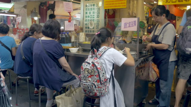 Customers eat at noodle soup food stall in Taipei, Taiwan