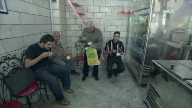 ws customers eating ice cream in parlor, iran - präsentation hinter glas stock-videos und b-roll-filmmaterial