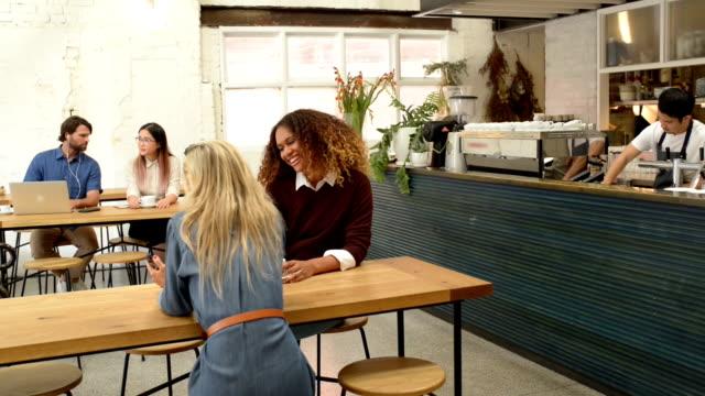 Customers Enjoy Coffee in Cafe