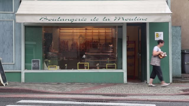 customers enter a bakery in rodez, france, on thursday, aug. 8, 2013., a customer leaves a bakery carrying a bundle of baguettes, an employee... - bakery stock videos & royalty-free footage