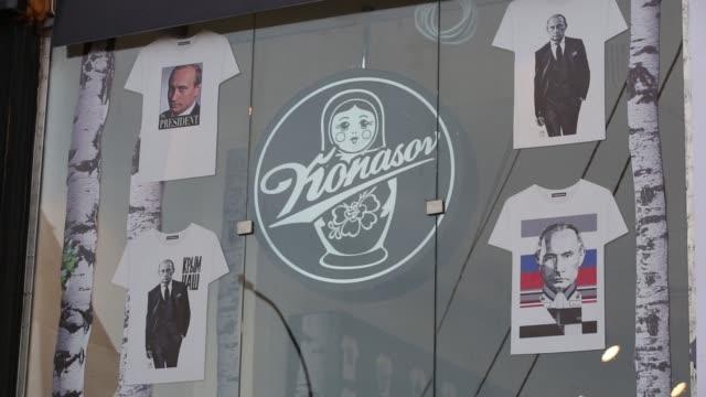 vídeos de stock, filmes e b-roll de customers enter an alexander konasov clothing store advertising their patriot collection featuring patriotic images of russias president vladimir... - rodeando