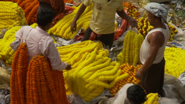 Customers examine yellow and orange flower garlands offered by market vendors.