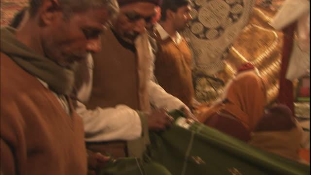 Customers haggle over blanket on market stall, Allahabad, Uttar Pradesh, India