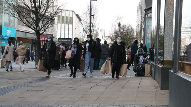 customers leaving clothing store with shopping bags as lockdown ended in birmingham, england, uk, on monday, april 4, 2021. - clothing stock videos & royalty-free footage