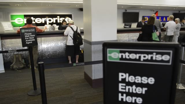 "vídeos de stock e filmes b-roll de customers line up at an enterprise rent a car location in san francisco, california on september 29 close up of ""enterprise"" signage with customers... - aluguer de automóveis"