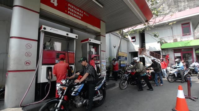 customers line up to refuel their motorcycles at a pt pertamina gas station in nusa dua bali indonesia on wednesday aug 27 an attendant refuels a... - gas station attendant stock videos and b-roll footage