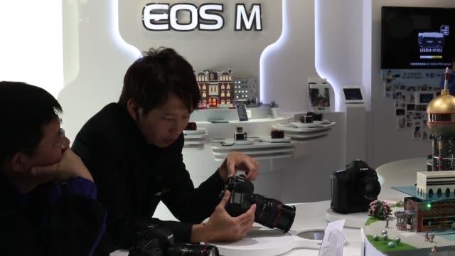 customers looking at digital dslr cameras in canon showroom, demonstrated by canon assistants canon showroom in hong kong on january 29, 2013 in hong... - digital spegelreflexkamera bildbanksvideor och videomaterial från bakom kulisserna