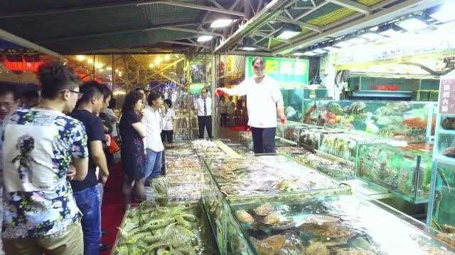 WS PAN Customers looking at fresh fish in market / Hong Kong, China