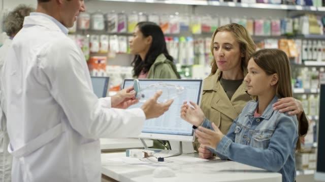 vidéos et rushes de les clients regardant le pharmacien utilisant l'inhalateur d'asthme - inhalateur