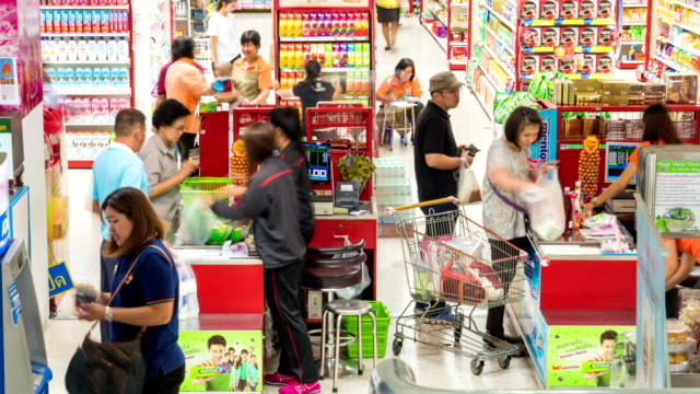 Customers paying for goods at the check counter in supermarket