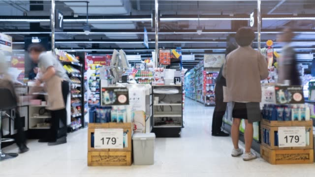 customers paying for goods at the check counter in supermarket - checkout stock videos & royalty-free footage
