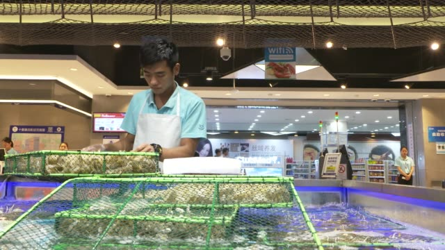 Customers push carts past live seafood in water tanks at an Alibaba Group Holding Ltd Hema Store in Shanghai China on Tuesday Sept 12 Customers look...