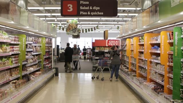 customers push their shopping carts beneath promotional signs offering great prices as they browse for goods inside a sainsburys supermarket store... - dairy product stock videos & royalty-free footage