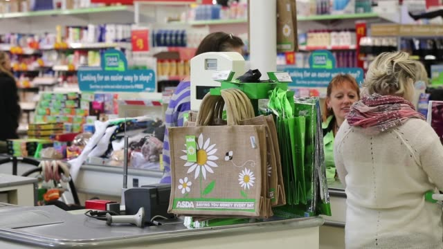 Customers push their shopping carts through an aisle inside an Asda supermarket the UK retail arm of WalMart Stores Inc in Watford UK on Thursday Oct...
