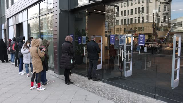 customers queue to enter a store of clothing retailer c&a after a sales assistant opens the doors for the first time since december as lockdown... - sales occupation stock videos & royalty-free footage