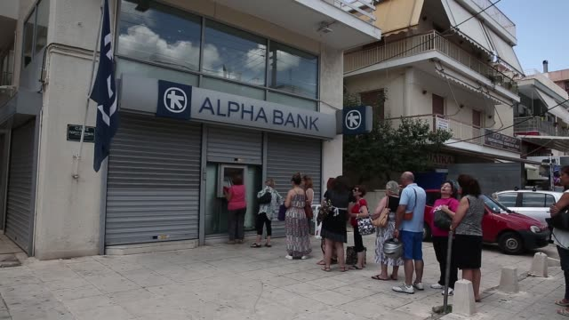 Customers queue to use an automated teller machine outside a Alpha Bank branch in Athens Greece on Monday June 29 2015